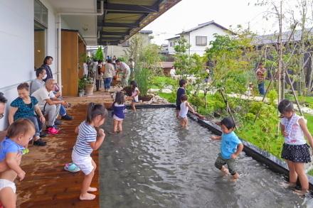 縁側の水場で遊ぶ子供たち