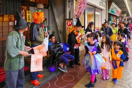 お菓子を貰いながら商店街を歩く参加者