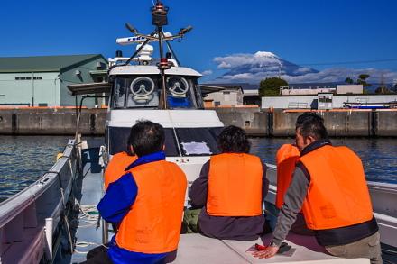 出航する渡船と富士山の風景