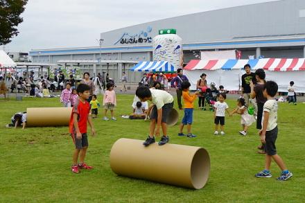 大きな紙管で遊ぶ子供たち
