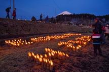 点火された竹灯籠を眺める人々