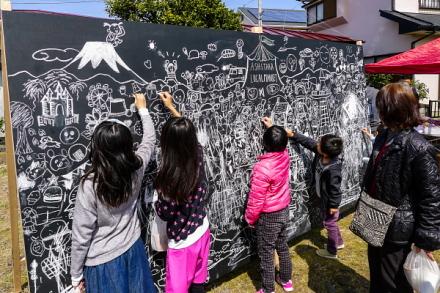 大きな黒板に絵を描く子供たち
