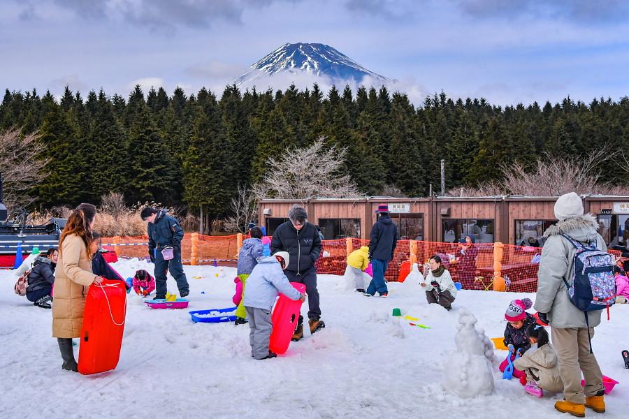 富士山をバックに賑わう雪の丘
