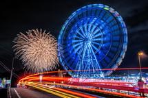 観覧車と車の光跡そして花火の風景