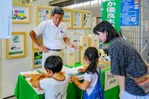 環境関連の展示を見る親子連れ
